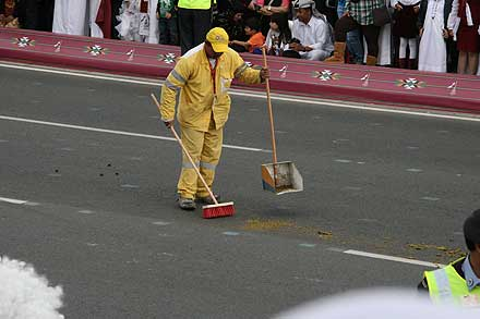 Street cleaner sweeping up camel dung